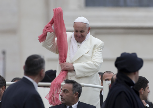 Pope Francis holds a pink scarf thrown to him by faithful as he arrives for his weekly general audience in St. Peter's Square at the Vatican, Wednesday, Nov. 27, 2013. Francis is bundling up for the cold snap belting Italy, donning a white double-breasted winter coat and scarf. Several times Wednesday, the pope used his sleeves as a muffler to keep his hands warm amid temperatures that dipped to freezing with the wind chill factored in. (AP Photo/Alessandra Tarantino)