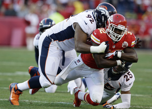 Denver Broncos defensive tackle Sylvester Williams (92) tackles Kansas City Chiefs running back Cyrus Gray (32) during the first half of an NFL football game, Sunday, Dec. 1, 2013, in Kansas City, Mo. (AP Photo/Charlie Riedel)