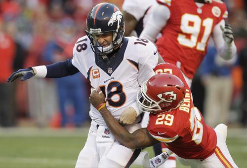 Kansas City Chiefs strong safety Eric Berry (29) tackles Denver Broncos quarterback Peyton Manning (18) after Manning through a pass during the first half of an NFL football game, Sunday, Dec. 1, 2013, in Kansas City, Mo. (AP Photo/Ed Zurga)