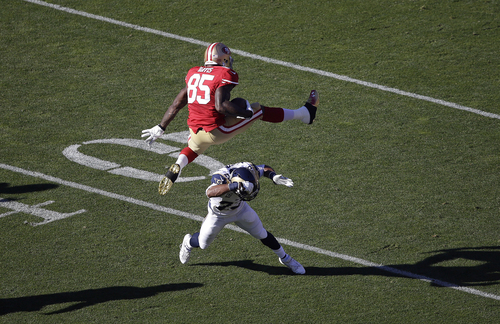 San Francisco 49ers tight end Vernon Davis (85) jumps over St. Louis Rams free safety Rodney McLeod during the first quarter of an NFL football game in San Francisco, Sunday, Dec. 1, 2013. (AP Photo/Tony Avelar)