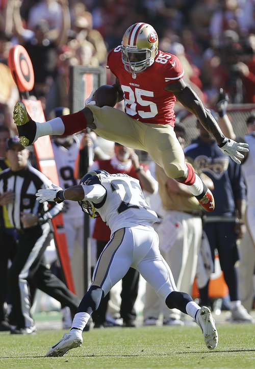San Francisco 49ers tight end Vernon Davis (85) jumps over St. Louis Rams free safety Rodney McLeod (23) during the first quarter of an NFL football game in San Francisco, Sunday, Dec. 1, 2013. (AP Photo/Marcio Jose Sanchez)