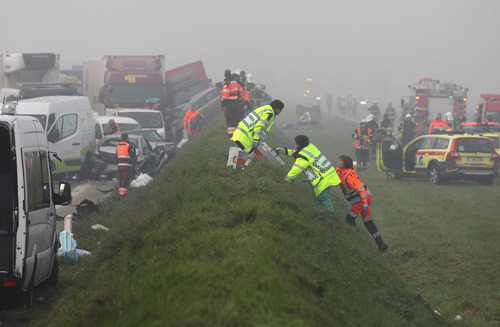 Medics carry equipment to a crash scene on the A19 highway in Zonnebeke, western Belgium, Tuesday, Dec.3, 2013.  Dozens of cars and trucks crashed in dense morning fog, killing at least one and injuring dozens more. (AP Photo/Yves Logghe)