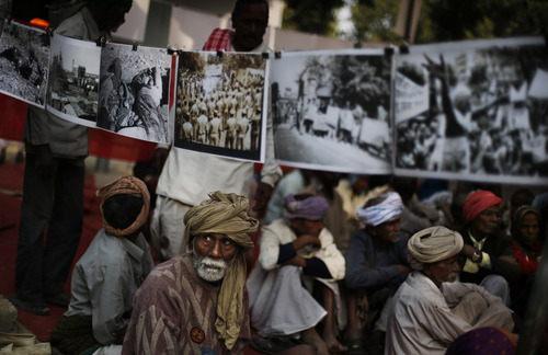 Survivors and their supporters sit next to photographs of the Bhopal gas disaster displayed during a protest on the anniversary of the tragedy near the Indian parliament in New Delhi, India, Tuesday, Dec. 3, 2013. On this day in 1984, thousands of people died after a cloud of methyl isocyanate gas escaped from a pesticide plant operated by a Union Carbide subsidiary in Bhopal in central India. (AP Photo/Altaf Qadri)