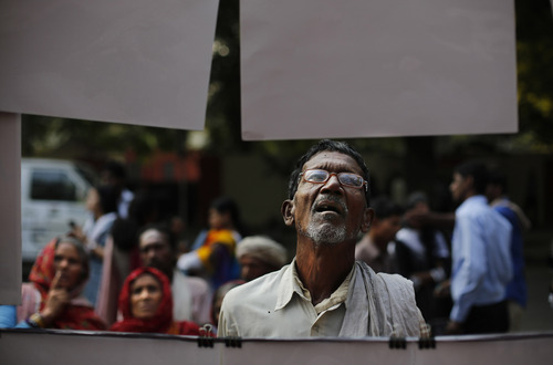 An Indian man looks at photographs of the Bhopal gas disaster displayed during a protest on the anniversary of the tragedy near the Indian parliament in New Delhi, India, Tuesday, Dec. 3, 2013. On this day in 1984, thousands of people died after a cloud of methyl isocyanate gas escaped from a pesticide plant operated by a Union Carbide subsidiary in Bhopal in central India. (AP Photo/Altaf Qadri)