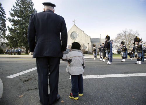 A police officer holds his son's hand outside a church during the funeral for Michael Feeney Tuesday, Dec. 3, 2013, in Ridgewood, N.J. Feeney, 10, was named Ridgewood's honorary police chief for 2013 before succumbing to cancer last week. He had been struggling for four years with Ewing's sarcoma, a rare, aggressive and often fatal bone cancer that usually develops in children and young adults. (AP Photo/Mel Evans)