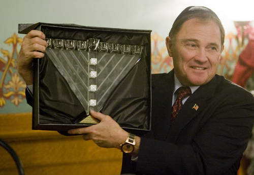 Keith Johnson   The Salt Lake Tribune  Utah Governor Gary Herbert holds a crystal menorah presented to him by Rabbi Benny Zippel of Chabad Lubavitch of Utah during the menorah-lighting ceremony at the Governor's Mansion, December 2, 2013 in Salt Lake City. Community and religious leaders were present for the event.