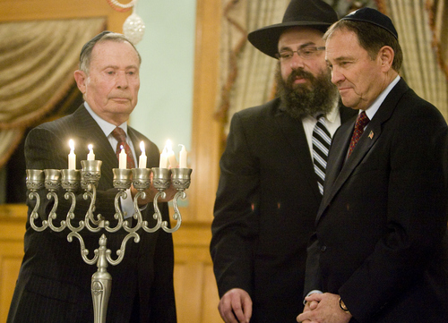 Keith Johnson | The Salt Lake Tribune  Utah Governor Gary Herbert, right, and Rabbi Benny Zippel of Chabad Lubavitch of Utah watch as former U.S. Ambassador John Price, whose family fled Nazi Germany when he was 5 years old, lights the menorh during the menorah-lighting ceremony at the Governor's Mansion, December 2, 2013 in Salt Lake City. Community and religious leaders representing many faiths were present for the event.