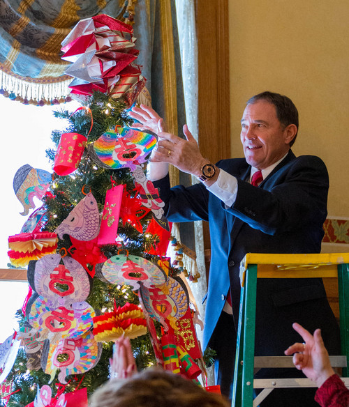 Trent Nelson  |  The Salt Lake Tribune Gov. Gary Herbert puts the final touch, a paper-folded star, on the top of the tree. Students from the Chinese immersion program at Stewart Elementary decorated a Christmas tree at the governor's mansion in Salt Lake City, Tuesday December 3, 2013.