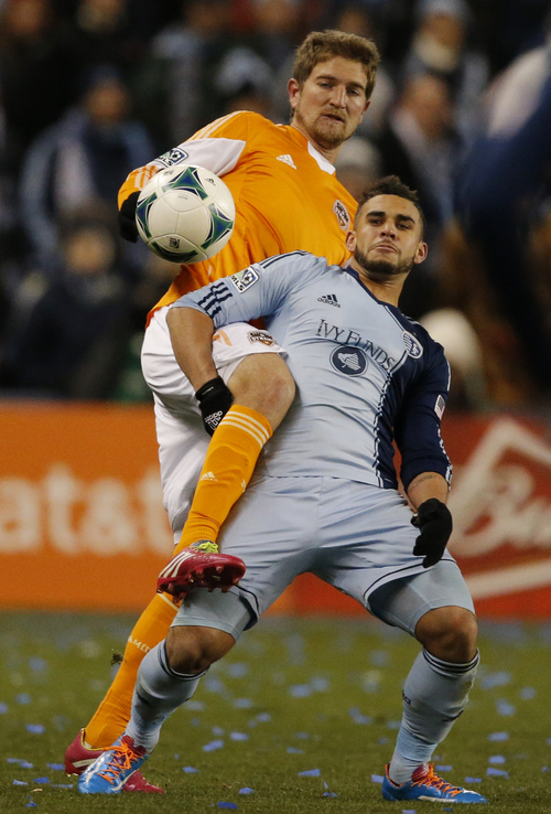 Sporting KC forward Dom Dwyer, front, and Houston defender Bobby Boswell, back, get tangled while playing the ball during the first half of an MLS playoff soccer match in Kansas City, Kan., Saturday, Nov. 23, 2013. (AP Photo/Orlin Wagner)