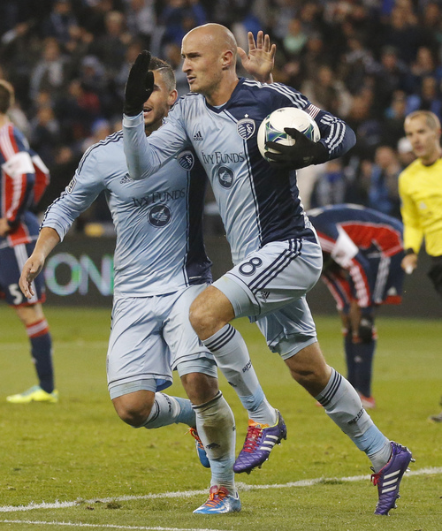 Sporting Kansas City defender Aurelien Collin (78) is congratulated by teammate Dom Dwyer, left, during the first half of an MLS playoff soccer match against the New England Revolution in Kansas City, Kan., Wednesday, Nov. 6, 2013. (AP Photo/Orlin Wagner)