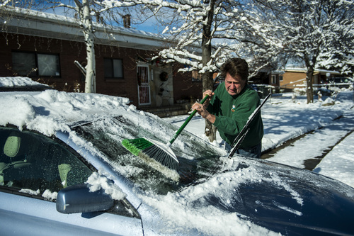 Chris Detrick  |  The Salt Lake Tribune Bill Brown uses a broom to clean off snow on his car in Salt Lake City Wednesday Dec. 4, 2013.