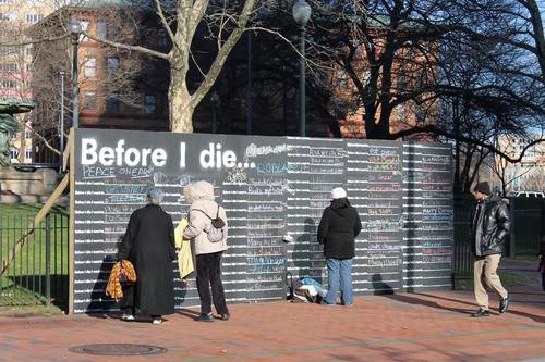 "In this Nov. 29, 2013 photo, people finish the sentence ""Before I die . . ."" on a large blackboard in Providence, R.I.  Since 2011, 400 such walls have gone up in the United States as well as in 60 other countries. The global phenomenon has oversize blackboards, painted on buildings and freestanding displays that invite those passing by to complete the sentence. (AP Photo/Michelle Smith)"