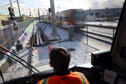 Francisco Kjolseth  |  The Salt Lake Tribune Train operator Mark Lococo passes a TRAX train while UTA has a media preview ride-along on the new Sugar House Streetcar on Wednesday, Dec. 4, 2013. Opening ceremonies are scheduled for Thursday and it opens to the public Saturday.