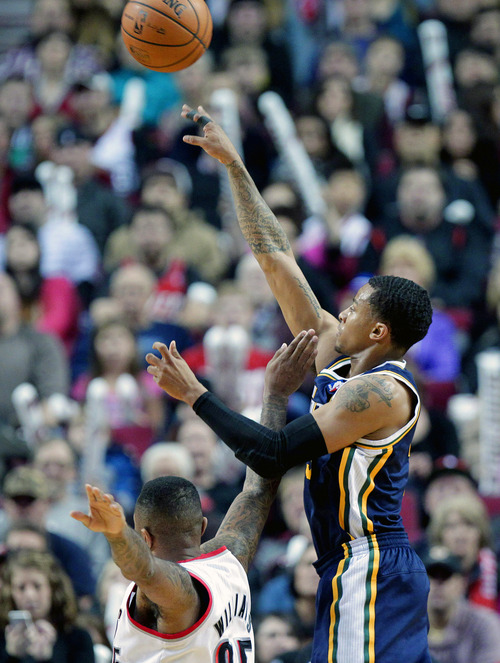 Utah Jazz guard Trey Burke, right, shoots over Portland Trail Blazers guard Mo Williams during the first half of an NBA basketball game in Portland, Ore., Friday, Dec. 6, 2013. (AP Photo/Don Ryan)
