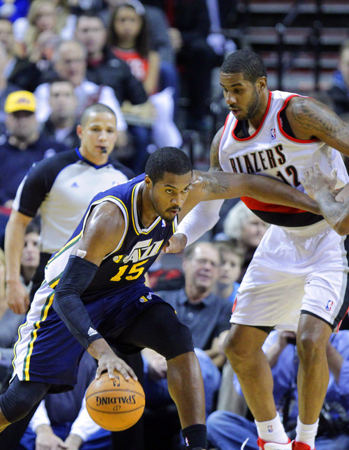 Utah Jazz forward Derrick Favors, left, drives on Portland Trail Blazers forward LaMarcus Aldridge during the first half of an NBA basketball game in Portland, Ore., Friday, Dec. 6, 2013. (AP Photo/Don Ryan)