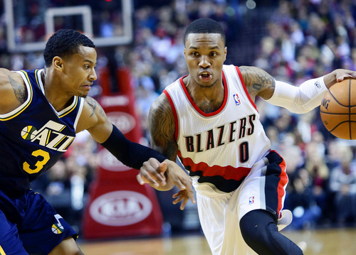 Portland Trail Blazers guard Damian Lillard, right, drives on Utah Jazz guard Trey Burke during the first half of an NBA basketball game in Portland, Ore., Friday, Dec. 6, 2013. (AP Photo/Don Ryan)