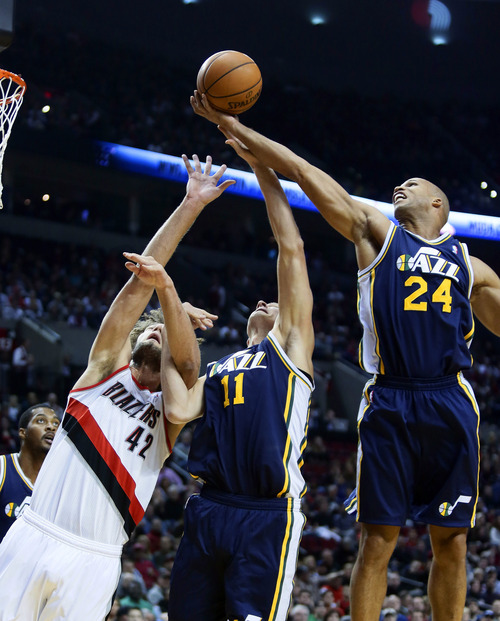 Portland Trail Blazers center Robin Lopez, left, battles for a rebound with Utah Jazz forward Richard Jefferson, right, and center Andris Biedrins, from Latvia, during the first half of an NBA basketball game in Portland, Ore., Friday, Dec. 6, 2013. (AP Photo/Don Ryan)