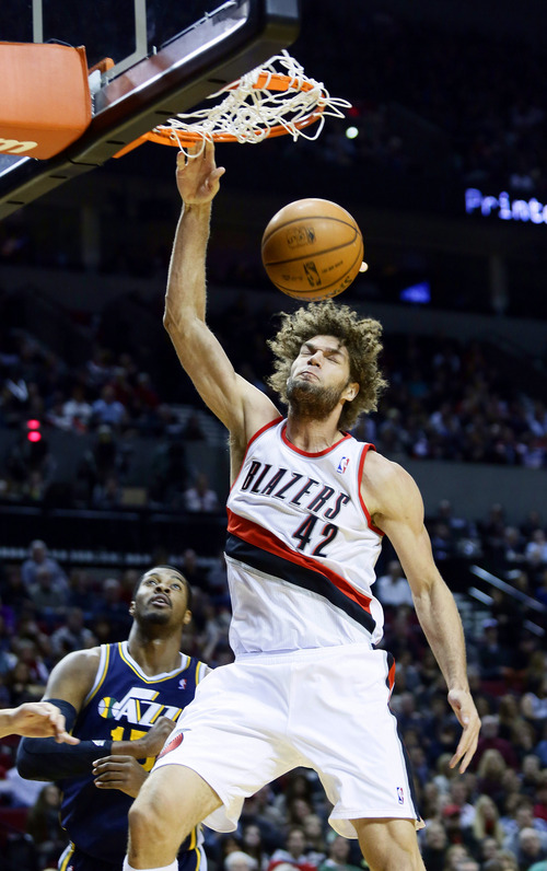 Portland Trail Blazers center Robin Lopez, right, scores against Utah Jazz forward Derrick Favors during the first half of an NBA basketball game in Portland, Ore., Friday, Dec. 6, 2013. (AP Photo/Don Ryan)