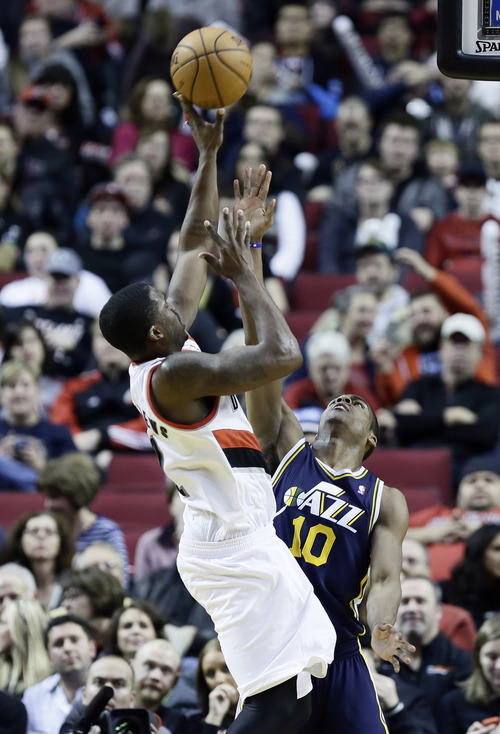 Portland Trail Blazers guard Wesley Matthews, left, shoots over Utah Jazz guard Alec Burks during the second half of an NBA basketball game in Portland, Ore., Friday, Dec. 6, 2013.  Wesley topped the Trail Blazers in scoring with 24 points as they beat Utah 130-98. (AP Photo/Don Ryan)