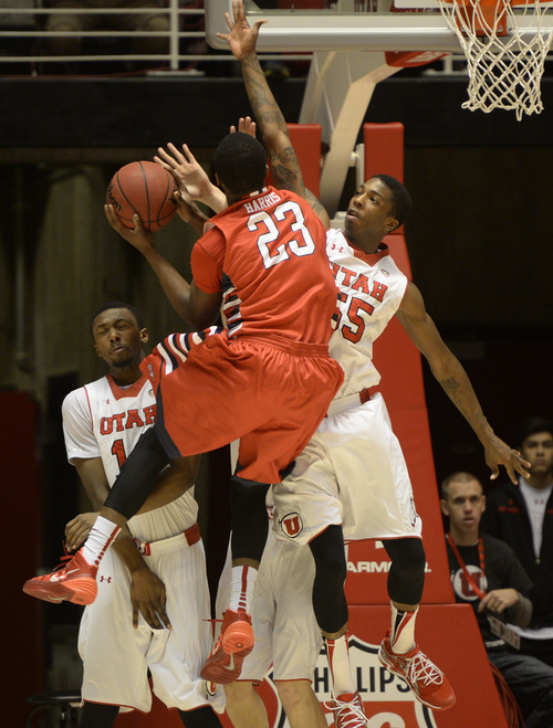 Rick Egan    The Salt Lake Tribune   Utah Utes guard Delon Wright (55) defends as Fresno State Bulldogs guard Marvelle Harris (23) takes the ball to the hoop, in basketball action Utah vs. Fresno State, in the Huntsman Center, Saturday, December 7, 2013.Harris was called for charging on the play.