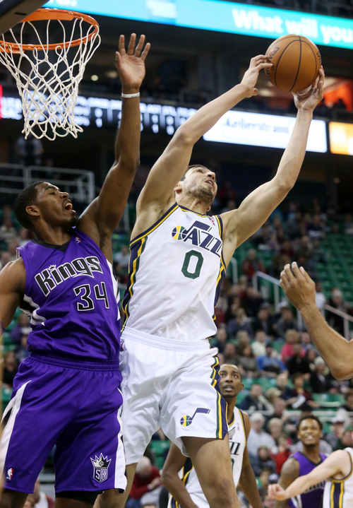 Utah Jazz's Enes Kanter (0) rebounds the ball over the hands of Sacramento Kings' Jason Thompson (34) in the first half of an NBA basketball game on Saturday, Dec. 7, 2013, in Salt Lake City. (AP Photo/Kim Raff)