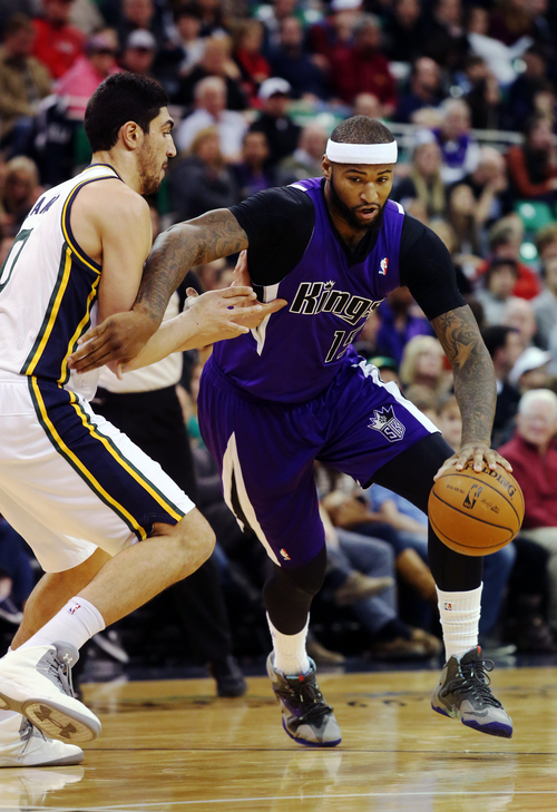 Utah Jazz's Enes Kanter, left, defends as Sacramento Kings' DeMarcus Cousins (15) drives the basket in the first half of an NBA basketball game on Saturday, Dec. 7, 2013, in Salt Lake City. (AP Photo/Kim Raff)