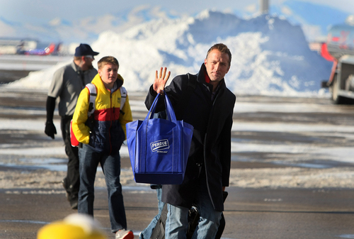 Scott Sommerdorf      The Salt Lake Tribune Real Salt Lake head coach Jason Kreis waves to fans who had braved the below-freezing temperatures to wait for the team to return. RSL players and coaches arrive in Salt Lake at the TAC Air sports terminal, Sunday December 8, 2013.