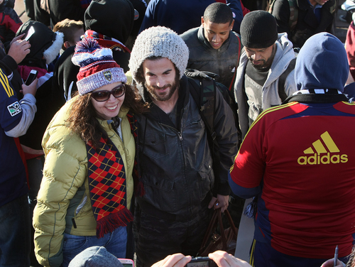 Scott Sommerdorf      The Salt Lake Tribune RSL midfielder Kyle Beckerman poses for a photo with a fan as he and other Real Salt Lake players and coaches as they make their way through a sea of fans after arriving in Salt Lake at the TAC Air sports terminal, Sunday December 8, 2013.