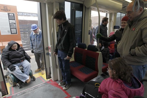 Leah Hogsten  |  The Salt Lake Tribune Everett Petersen, 16, (center) exits the S-Line at the Fairmont S-Line stop with his family. The new Sugar House Streetcar, or S-Line, held a free preview day for the public with free rides with a can of food, December 7, 2013.