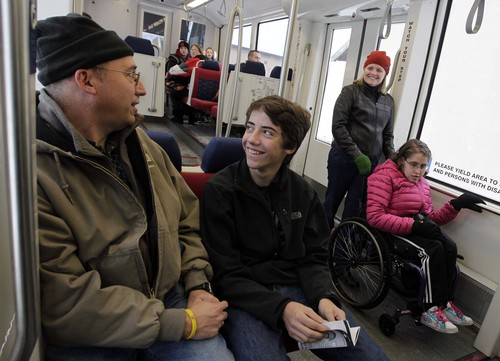 Leah Hogsten  |  The Salt Lake Tribune l-r David Petersen of Bountiful, son Everett, 16, wife Rosalie and daughter Ivy, 20, share a laugh while riding the train. The new Sugar House Streetcar, or S-Line, held a free preview day for the public with free rides with a can of food, December 7, 2013.