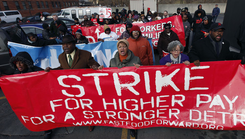 FILE - In this Thursday, Dec. 5, 2013 file photo, protesters rally for better wages at a Wendy's in Detroit.f.  Fast food chains are the epicenter of the battle over the minimum wage, with employees staging protests for an increase. (AP Photo/Paul Sancya, File)
