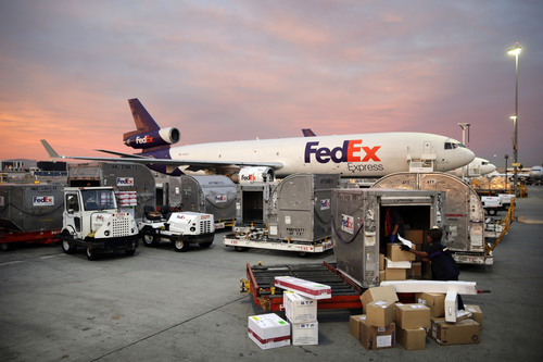 In this Monday, Dec. 2, 2013 photo, Brenda Thompson, right, loads packages into a container at the FedEx hub at Los Angeles International Airport in Los Angeles. Hiring usually gets a boost with the advent of holiday shopping, but online shopping has changed where  people are hiring. Transportation and warehouse jobs in places like FedEX and UPS jumped 30,500 in November. That's 50 percent greater than the November 2012 increase. (AP Photo/Jae C. Hong)