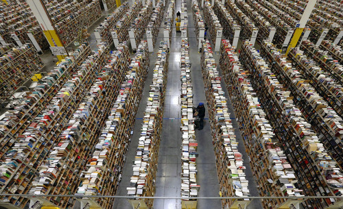 FILE - In this Monday, Dec. 2, 2013, file photo, an Amazon.com employee stocks products along one of the many miles of aisles at an Amazon.com Fulfillment Center in Phoenix. Holiday sales jobs are now likelier to be in warehouses and trucks than in retail stores. Amazon alone planned to hire 20,000 more holiday workers this year, according to the personnel firm Challenger, Gray & Christmas.  (AP Photo/Ross D. Franklin, File)