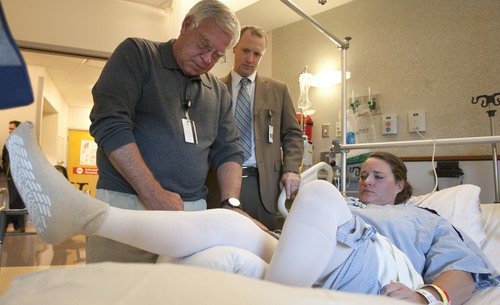 Steve Griffin  |  The Salt Lake Tribune Chris Pelt, an orthopedist at the University of Utah, center, looks on as his patient, Julie Harris,  works with physical therapist Chuck Graybill Thursday, November 7, 2013.