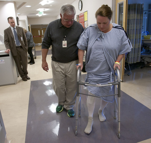 Steve Griffin     The Salt Lake Tribune Chris Pelt, an orthopedist at the University of Utah, left, looks on as his patient, Julie Harris,  works with physical therapist Chuck Graybill. Getting patients up and moving on the same day as their surgery speeds their recovery and cuts health costs.