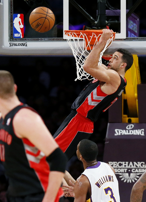 Toronto Raptors' Landry Fields misses a slam dunk attempt as Los Angeles Lakers' Shawne Williams (3) looks on during the first half of an NBA basketball game in Los Angeles, Sunday, Dec. 8, 2013. (AP Photo/Danny Moloshok)