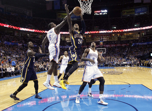 Oklahoma City Thunder center Kendrick Perkins (5) blocks a shot by Indiana Pacers forward Paul George (24) in the first quarter of an NBA basketball game in Oklahoma City, Sunday, Dec. 8, 2013. Oklahoma City won 118-94. (AP Photo/Sue Ogrocki)