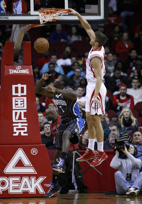 Houston Rockets small forward Chandler Parsons (25) dunks on Orlando Magic shooting guard Victor Oladipo (5) during the first quarter of an NBA basketball game on Sunday, Dec. 8, 2013, in Houston. (AP Photo/Bob Levey)