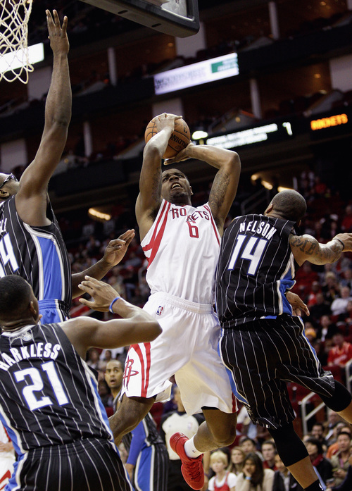 Houston Rockets power forward Terrence Jones (6) is fouled by Orlando Magic point guard Jameer Nelson (14) as he attempts a shot during the second half of an NBA basketball game on Sunday, Dec. 8, 2013, in Houston. (AP Photo/Bob Levey)