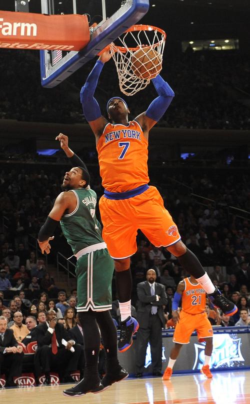 New York Knicks' Carmelo Anthony (7) dunks a basket over Boston Celtics' Jared Sullinger (7) during the first half of an NBA basketball game on Sunday, Dec. 8, 2013, in New York. The Celtics won 114-73. (AP Photo/Kathy Kmonicek)