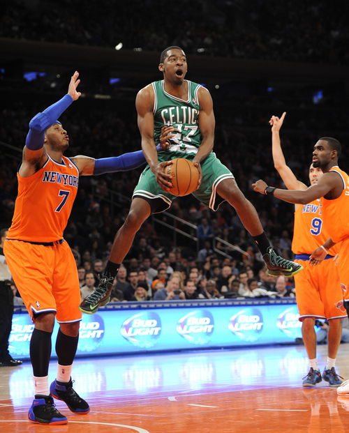 Boston Celtics' Jordan Crawford (27) leaps next to New York Knicks' Carmelo Anthony (7) after getting fouled during the second half an NBA basketball game on Sunday, Dec. 8, 2013, in New York. The Celtics won 114-73. (AP Photo/Kathy Kmonicek)