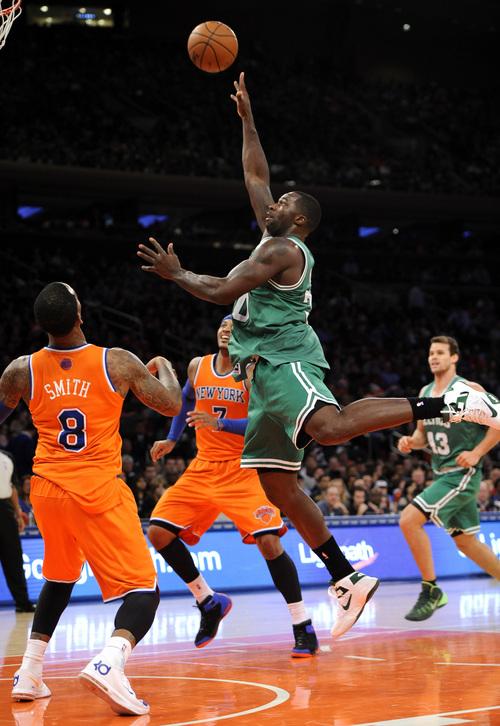 Boston Celtics' Brandon Bass (30) shoots over New York Knicks' J.R. Smith (8) and Carmelo Anthony (7) in the first half an NBA basketball game on Sunday, Dec. 8, 2013, in New York. The Celtics won 114-73. (AP Photo/Kathy Kmonicek)