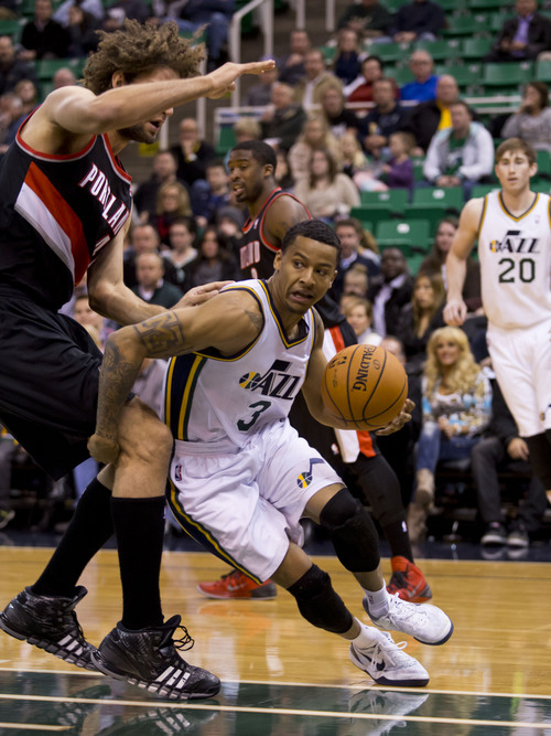 Lennie Mahler  |  The Salt Lake Tribune Jazz guard Trey Burke looks to pass the ball as he drives around Portland's Robin Lopez in the first half of a game against the Portland Trailblazers on Monday, Dec. 9, 2013.