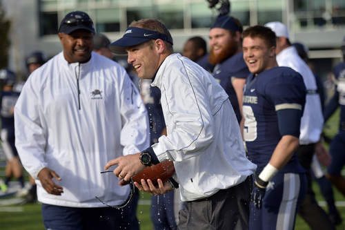 Chris Detrick  |  The Salt Lake Tribune Utah State Aggies head coach Matt Wells gets water dumped on him after the game at Merlin Olsen Field at Romney Stadium Saturday November 30, 2013.  Utah State defeated Wyoming 35-7. The Aggies will visit Fresno State in the title game next Saturday to complete their first season of MW competition.