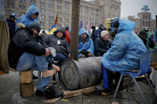 Pro-European Union activists warm themselves around a bonfire as they gather in Independence Square in Kiev, Ukraine, Tuesday, Dec. 10, 2013. Top Western diplomats headed to Kiev Tuesday to try to defuse a standoff between President Viktor Yanukovych's government and thousands of demonstrators, following a night in which police in riot gear dismantled protesters' encampments outside government buildings. (AP Photo/Alexander Zemlianichenko)