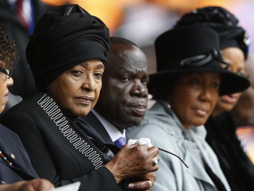 Winnie Madikizela-Mandela, left, Nelson Mandela's former wife, attends the memorial service for former South African president Nelson Mandela at the FNB Stadium in Soweto near Johannesburg, Tuesday, Dec. 10, 2013. (AP Photo/Matt Dunham)