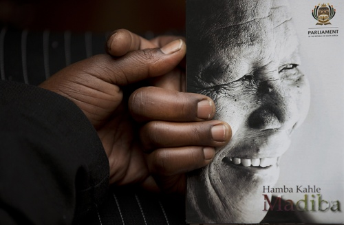 A man holds the official programme ahead of the memorial service for former South African president Nelson Mandela at the FNB Stadium in the Johannesburg, South Africa township of Soweto, Tuesday, Dec. 10, 2013. (AP Photo/Peter Dejong)