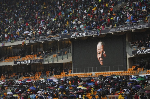 The face of Nelson Mandela is shown on a large billboard in the stands at the memorial service for former South African President Nelson Mandela at the FNB stadium in Johannesburg, South Africa Tuesday, Dec. 10, 2013. (AP Photo/Ben Curtis)