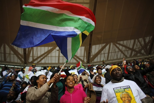 A woman waves a South African national flag ahead of the memorial service for former South African president Nelson Mandela at the FNB Stadium in Soweto, near Johannesburg, South Africa, Tuesday Dec. 10, 2013. (AP Photo/Markus Schreiber)