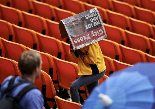 A woman covers herself from the rain as she arrives for the memorial service for former South African president Nelson Mandela at the FNB Stadium in Soweto, near Johannesburg, South Africa, Tuesday Dec. 10, 2013. (AP Photo/Ben Curtis)